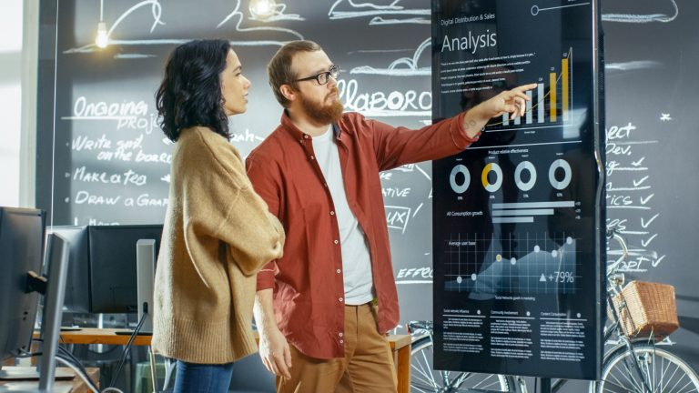 Man and woman looking at huge touch screen showing stats